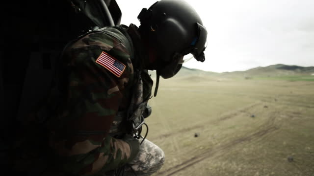 soldier looking out of landing helicopter - army stock-videos und b-roll-filmmaterial