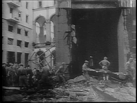 vídeos de stock e filmes b-roll de soldier looks out over destroyed city of naples / exterior of building, civilians stand in street nearby / bomb explosion / street filled with smoke... - bomba