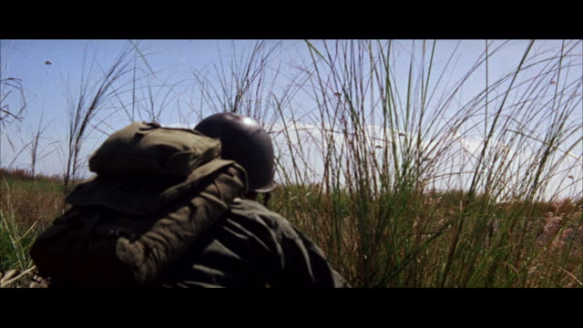 cu pan soldier lying in grass and many parachutes drifiting to ground  / tokyo, japan - 制服点の映像素材/bロール