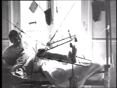 soldier lying in hospital bed with leg in traction, sitting up, drinking from a cup and demonstrating movement of leg up and down; small american... - ギプス点の映像素材/bロール