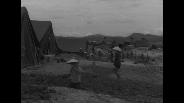 us soldier member of merrill's marauders walking past camera / supplies dropping by parachute from plane / ws military base workers in foreground... - myanmar stock videos & royalty-free footage