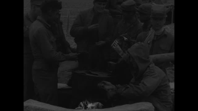 soldier of the 21st regiment, 24th us division chops wood / troops stand in small groups around bonfires / soldiers huddle around fire; one reads... - wood material stock videos & royalty-free footage