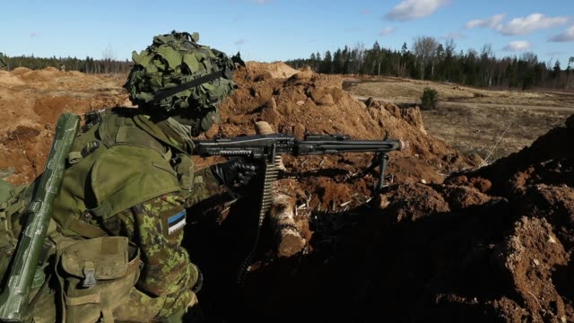 a soldier of the estonian defence forces aims his machine gun to defend his position during a joint military combat exercise with us army troops on... - estonia stock videos & royalty-free footage