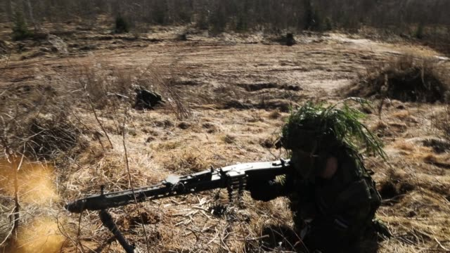 a soldier of the estonian defence forces fires his machine gun to defend his position during a joint military combat exercise with us army troops on... - military exercise stock videos and b-roll footage