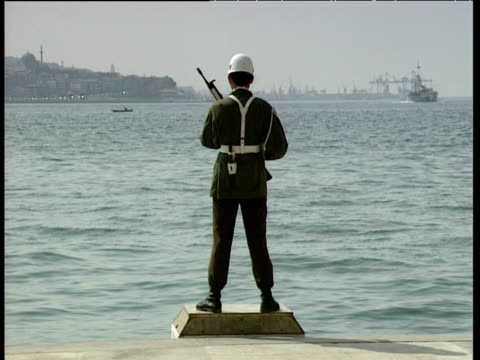 vidéos et rushes de soldier on duty standing on small platform looking out to sea pleasure boat passes by dolmabahce palace istanbul - turquie