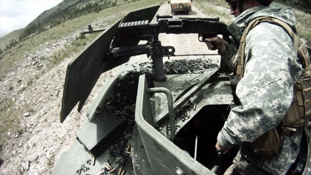 stockvideo's en b-roll-footage met soldier on humvee trains with gun - humvee