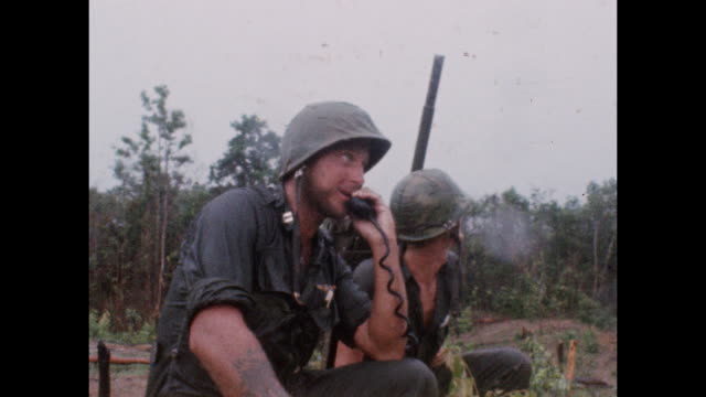 soldier on phone on battle field during the vietnam war as wounded troops are evacuated from combat zone near the 17th parallel. 1966. - vietnam war stock videos & royalty-free footage