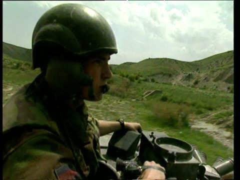 stockvideo's en b-roll-footage met soldier on tank as it drives down dirt road pan right to reveal dirt road albania 1999 - ruimte exploratie