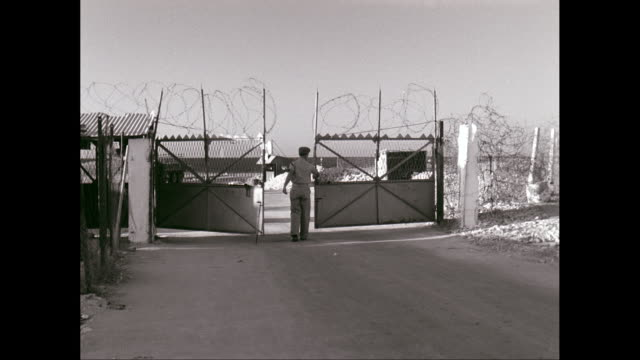 WS Soldier opening gate of military building area / United States
