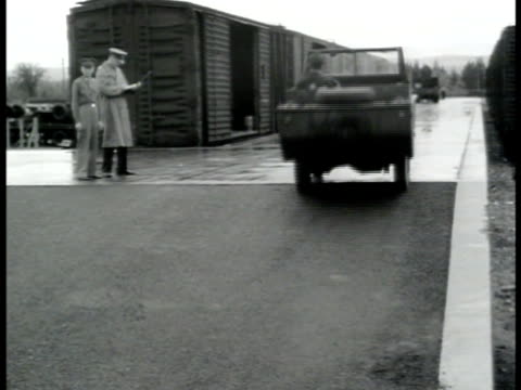 us soldier patrolling track several gpas driving up ramp to train boxcars ws line of gpas us officers overseeing men loading barrels into boxcars wwii - c119gs stock videos & royalty-free footage