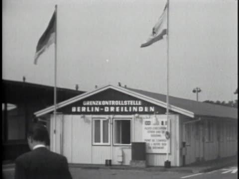 soldier patrols the border crossing between east and west berlin. - 1950 1959 stock-videos und b-roll-filmmaterial