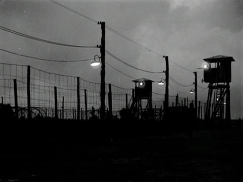 a soldier patrols the perimeter fence of a concentration/prison camp - concentration camp stock videos & royalty-free footage