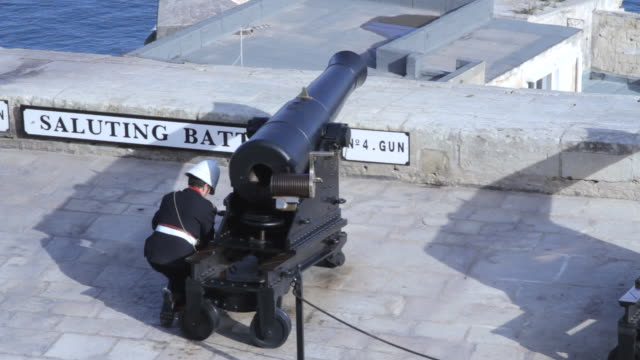 a soldier places a blank charge into a cannon on valletta's grand harbour. - festung stock-videos und b-roll-filmmaterial