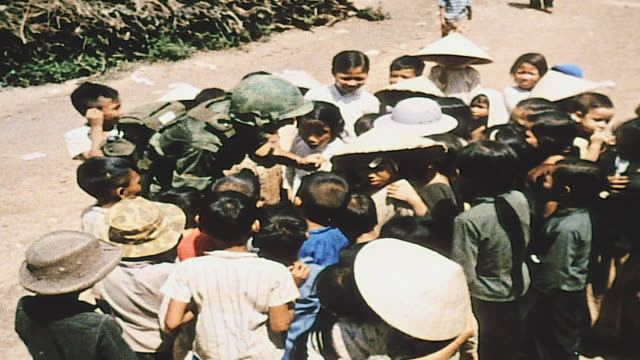 soldier playing and eating candy with pack of young villagers / vietnam - 50 seconds or greater stock videos & royalty-free footage