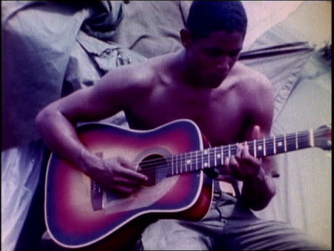 a soldier playing guitar in front of tent / soldiers pitching tent / soldier cleaning gun / soldier relaxing on ground weapon beside him - vietnam war stock videos & royalty-free footage