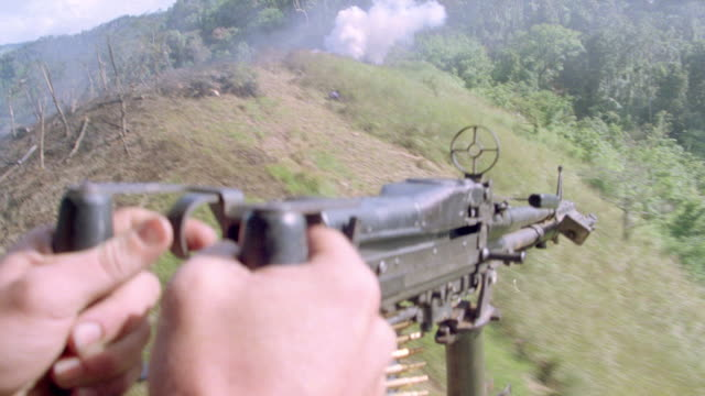 a soldier points a machine gun out the side of a low flying helicopter. - vietnam war stock videos & royalty-free footage