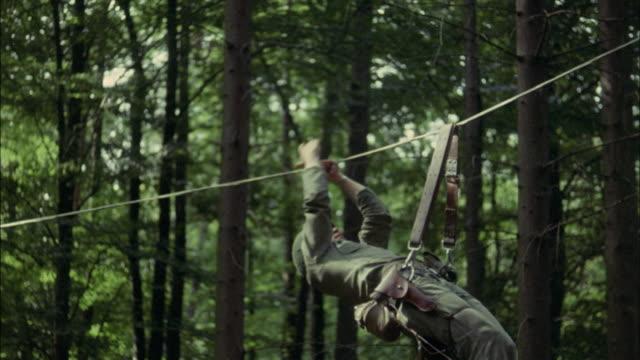 vídeos de stock e filmes b-roll de 1967 ms pan montage ws la soldier pulling himself on rope between trees - ponte suspensa