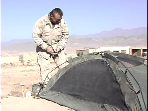 vídeos de stock e filmes b-roll de soldier pulling out tent stakes and packing tent at military base / afghanistan - operação enduring freedom