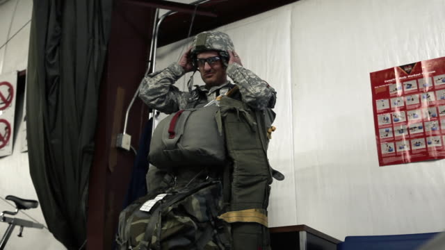 vídeos de stock, filmes e b-roll de soldier putting on glasses and strapping on helmet before parachuting. - uniforme militar