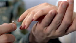 Soldier putting ring on female hand, proposing to girlfriend, couple marriage