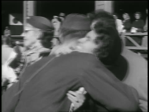 b/w 1954 soldier returning from korean war hugging woman as man pats him on back / seattle - 1954 bildbanksvideor och videomaterial från bakom kulisserna