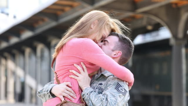 vídeos de stock e filmes b-roll de ms pan soldier returning from war, hugging and kissing woman at train station / richmond, virginia, united states - soldado exército
