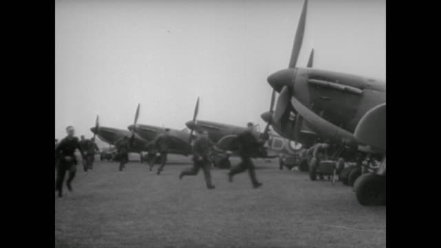 wwii a soldier rings a bell bringing out the members of the royal air force to board their spitfire planes - luftwaffe stock-videos und b-roll-filmmaterial