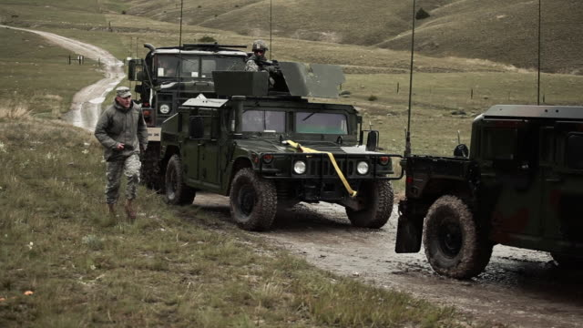 stockvideo's en b-roll-footage met soldier running along side of convoy. - humvee