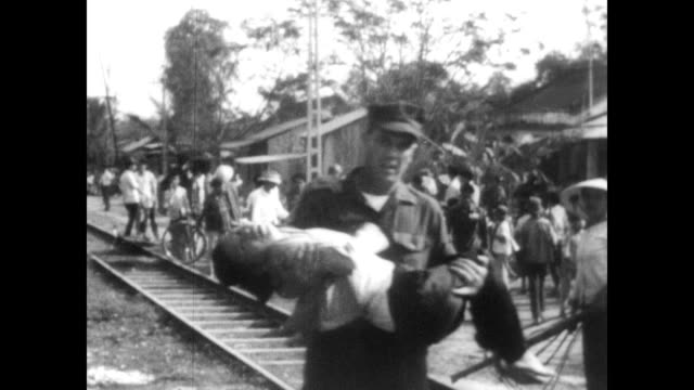 / soldier running with injured girl in his arms / people carrying wounded into ambulances / people milling about, dazed and confused / american... - vietnam war stock videos & royalty-free footage