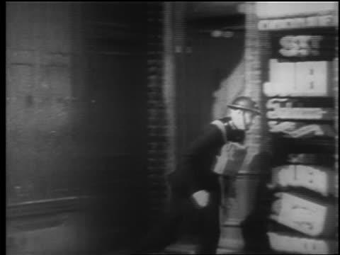vidéos et rushes de soldier runs from doorway past store / london blitz / educational - 1940