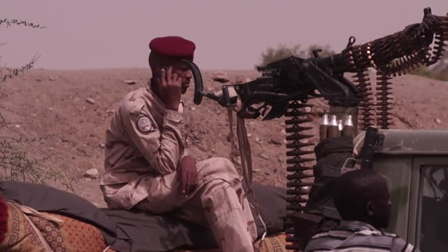 Soldier sat by tank on his mobile phone and close up of weapons as military stay in control in Khartoum Sudan