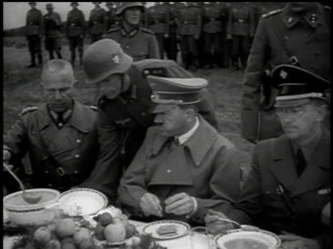 vidéos et rushes de ms soldier serving hitler a dish as dictator eats with his hands among wehrmacht officers / sudetenland czechoslovakia - wehrmacht