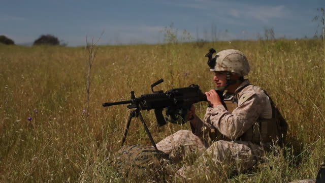 MS Soldier sits with heavy machine gun keeping watch AUDIO / Camp Pendleton, CA, United States
