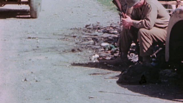 soldier sitting holding his rifle jeep driving by and dropping off a newspaper soldier reading headline 'victory' and soldier jumping and cheering - 1945 stock-videos und b-roll-filmmaterial