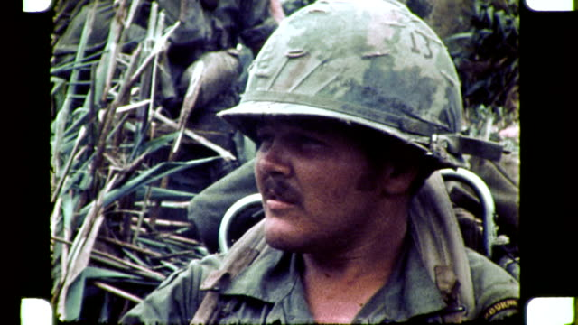 / cu of soldier sitting in grass smokes cigarette / soldiers in uniform holding guns - guerra del vietnam video stock e b–roll