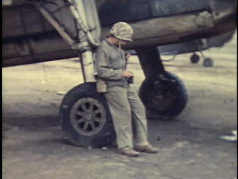 soldier sitting near an airplane while drinking from a can / iwo jima japan - battle of iwo jima stock videos and b-roll footage