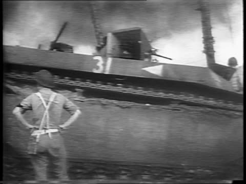 soldier standing as tank passes by burning field / soldiers and tanks on the beach / soldier walking past camera, smoke rising in the air / soldiers... - militärisches landfahrzeug stock-videos und b-roll-filmmaterial