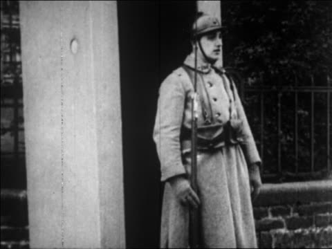 b/w 1929 soldier standing at attention in front of guard house / germany / newsreel - 1920 1929 stock-videos und b-roll-filmmaterial
