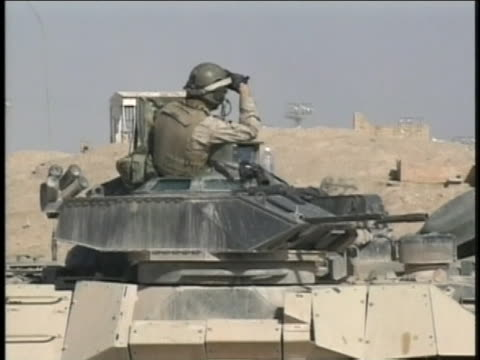 soldier standing atop a tank looks out over the desert in iraq. - (war or terrorism or election or government or illness or news event or speech or politics or politician or conflict or military or extreme weather or business or economy) and not usa stock videos & royalty-free footage