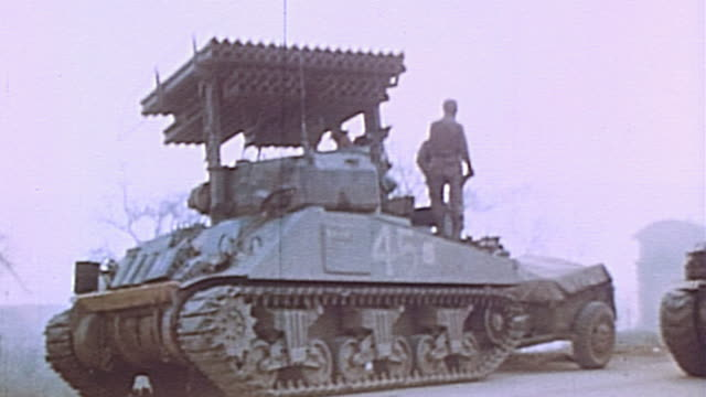 stockvideo's en b-roll-footage met la soldier standing atop us army engineering m4 sherman tank variant on side of dirt road with another sherman passing by during wwii european... - pantservoertuig