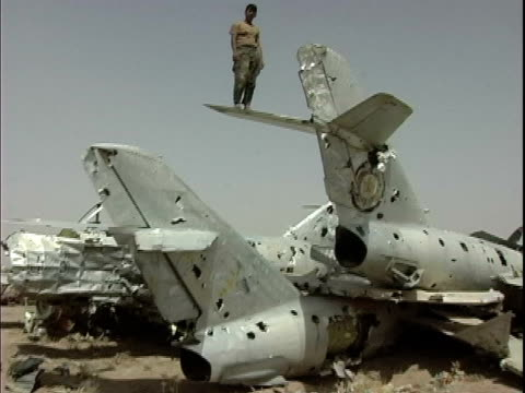 vídeos de stock e filmes b-roll de soldier standing atop wing of badly damaged military airplane / afghanistan - operação enduring freedom