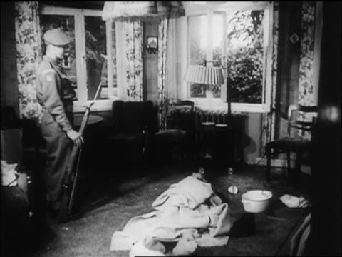 b/w 1945 soldier standing next to body of himmler on floor after suicide / newsreel - 1945 stock-videos und b-roll-filmmaterial