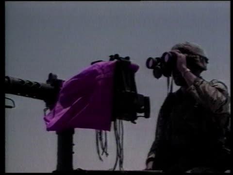 soldier standing next to machine gun covered with pink cloth looking through binoculars / saudi arabia - operation desert storm bildbanksvideor och videomaterial från bakom kulisserna