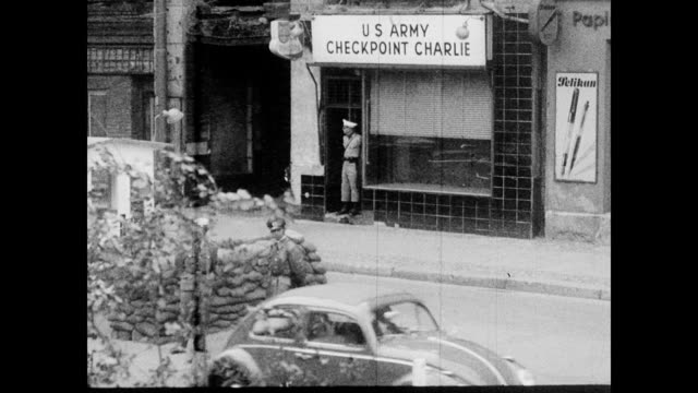 / soldier stands in doorway with sign above that reads 'US ARMY CHECKPOINT CHARLIE' / wider shot of Checkpoint Charlie showing American flag a wall...