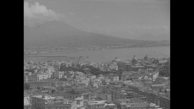 soldier stands on hill looking out over naples, pan across city and bay of naples / view from behind of two soldiers standing on hill looking out... - world war ii video stock e b–roll