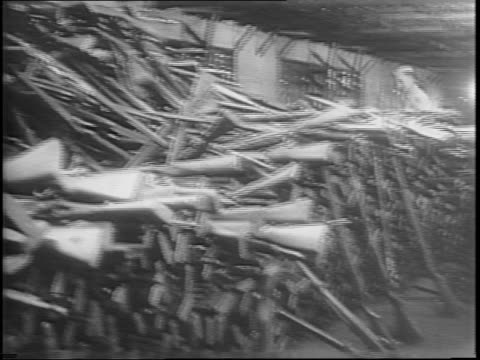 a soldier stands over several small piles of rifles tied into bundles / japanese soldiers put the bundles into heaps / another soldier stands guard... - narrow stock videos & royalty-free footage