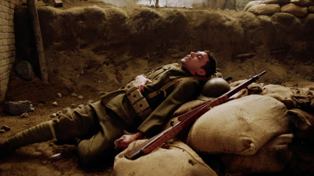 MS soldier suffering from wound in a trench with explosion in background (Sepia color tone)