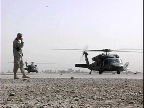 soldier talking on walkietalkie near blackhawk military helicopters at baghdad airport / baghdad iraq / audio - 2007 stock videos & royalty-free footage