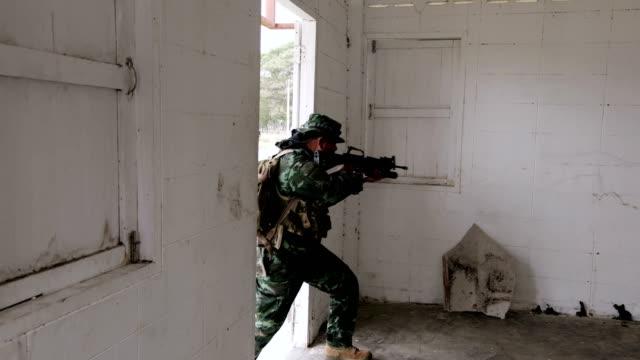 soldier team breaking into derelict building - centro commerciale suburbano video stock e b–roll
