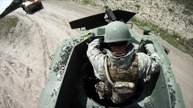 Soldier telling humvee driving there is a shortage of ammo